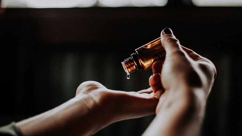 cbd bottle dropping into a palm